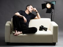 Exhaustion. Photo of tired photographer sitting on sofa Royalty Free Stock Image