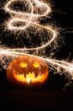 Exhibición de la calabaza de Halloween con la cara y las bengalas asustadizas Imagenes de archivo