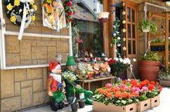 Exhibición de la floristería que contiene las flores y los gnomos del jardín Fotos de archivo