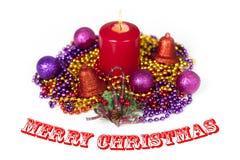 Exhibición de la Navidad con una vela roja que quema en el medio de cadenas y de chucherías Foto de archivo libre de regalías