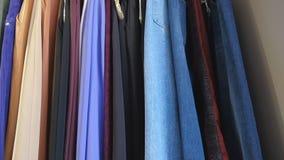 Exhibición de la ropa de la segunda mano en el estante para la caridad, donación, reutilizando o revendiendo para la segunda vida almacen de metraje de vídeo