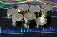 Exhibición de la tableta de Digitaces con el gráfico y la pila de monedas Imágenes de archivo libres de regalías