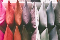 Exhibición de las almohadas de la variedad en el estante para los accesorios del sofá Imagen de archivo