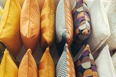 Exhibición de las almohadas de la variedad en el estante para los accesorios del sofá Imagen de archivo libre de regalías