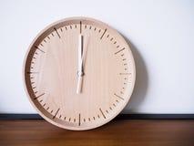 Exhibición de madera del reloj en el fondo blanco de la pared Fotografía de archivo