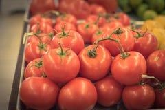 Exhibición jugosa de los tomates del racimo en el mercado del granjero con la muestra del precio Foto de archivo libre de regalías