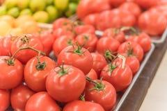 Exhibición jugosa de los tomates del racimo en el mercado del granjero con la muestra del precio Fotografía de archivo