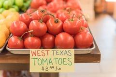 Exhibición jugosa de los tomates del racimo en el mercado del granjero con la muestra del precio Fotos de archivo