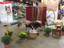 Exhibición pasada de moda de las materias textiles que ofrece algodón, un telar, una rueda de hilado, y la máquina de coser en un Fotografía de archivo libre de regalías