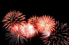 Exhibición roja y blanca de los fuegos artificiales en fondo oscuro del cielo Foto de archivo