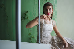 Exhibit. Artistic conceptual portrait of fashionable girl posing in an winter garden in vintage dress. The girl as an element of the winter garden, locked in as Royalty Free Stock Photography