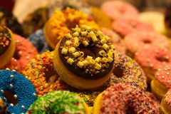 Exhibition of colorful donuts decorated with fancy crumbles in the market hall of Rotterdam, Netherlands royalty free stock image