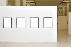 Exhibition with four empty frames on white walls Stock Images
