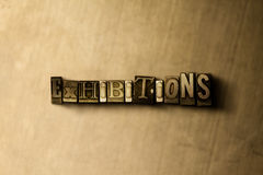 EXHIBITIONS - close-up of grungy vintage typeset word on metal backdrop Royalty Free Stock Images