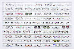 Exhibitor of glasses. Consisting of shelves of fashionable glasses shown on a wall at the optical shop Stock Images