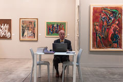 Exhibitor at Miart 2014 in Milan, Italy. MILAN, ITALY - MARCH 28: Exhibitor in his stand at Miart, international exhibition of modern and contemporary art on Royalty Free Stock Image