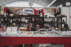 Exhibitor sitting in his stand at Militalia in Milan, Italy Stock Images
