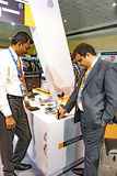 Exhibitors testing the hand held gold tester at IIJS. Many multinational companies exhibited their machinery at the IIJS 2015. One of the exhibitors are seen Royalty Free Stock Images