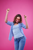 Exhilarate young hipster spends time with pleasure. Mid shot of an exhilarate young hipster spends time with pleasure. Female posing over pink background Royalty Free Stock Image