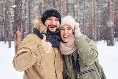 Exhilarated husband with thumb up hugging wife during the snowfa. Close-up of exhilarated husband with thumb up hugging wife during the snowfall in the forest Stock Photos