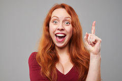 Exhilarated woman comes up with idea. Close-up of exhilarated woman with raised index finger coming up with idea. Woman isolated over gray background Stock Photography