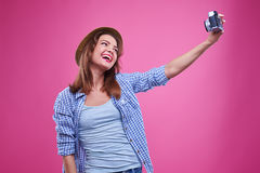 Exhilarated woman smiling while making selfie photo. Mid shot of exhilarated woman smiling while making selfie photo. Wearing checked shirt and straw hat Stock Image