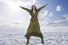 Exhilarated woman standing in snowy field.  Stock Photo