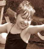 Exhilarating 2. Cute little girl plays outside in the sprinkler Stock Image