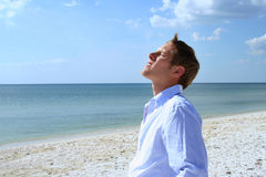 Exhilaration. Man lifting his face to sun on beach royalty free stock image