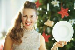 Exibição à moda de sorriso da dona de casa que serve a placa de jantar branca imagem de stock royalty free