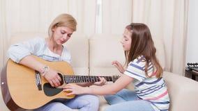 Exibição da filha a sua mãe como jogar uma música na guitarra vídeos de arquivo