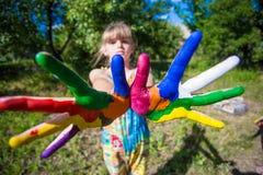 A exibição da menina pintou as mãos, foco nas mãos Mãos pintadas brancas de passeio Imagens de Stock