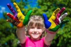 A exibição da menina pintou as mãos, foco nas mãos Mãos pintadas brancas de passeio Imagens de Stock Royalty Free