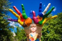 A exibição da menina pintou as mãos, foco nas mãos Mãos pintadas brancas de passeio Fotos de Stock Royalty Free