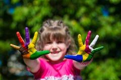 A exibição da menina pintou as mãos, foco nas mãos Mãos pintadas brancas de passeio Fotografia de Stock Royalty Free