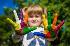 A exibição da menina pintou as mãos, foco nas mãos Mãos pintadas brancas de passeio Imagem de Stock