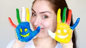 A exibição de sorriso da menina da menina do estudante do retrato pintou as mãos coloridas com sorrisos Educação do conceito, fac filme