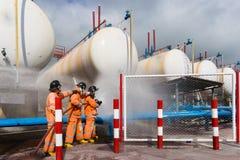 Exibição do bombeiro como usar sistemas de extinção de incêndios de um fogo em um fogo do treinamento Imagens de Stock