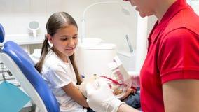 Exibição pediatra do dentista como usar a escova de dentes a seu paciente pequeno fotografia de stock