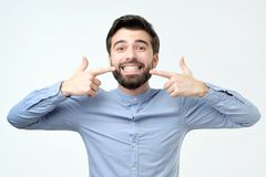 Exibição segura de sorriso do homem latino-americano e apontar com dentes e boca dos dedos foto de stock
