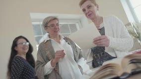 Exibição superior da mulher ao amigo suas fotos velhas e ambas que riem Terceira mulher que vem ver o que o faz rir três video estoque