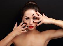 A exibição fêmea 'sexy' do modelo manicured as mãos perto da cara da composição Imagens de Stock Royalty Free