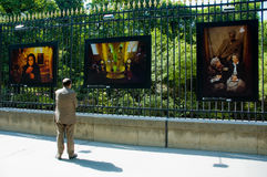 Exibited de whatching foto's van de mens op de omheining Stock Afbeeldingen