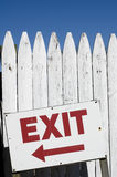 Exit. Sign on pickett fence arrow pointing left Stock Photo