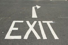 Exit. A tarmac road with the word, 'EXIT' and a directional arrow painted in white Royalty Free Stock Photo