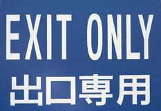EXIT ONLY. Sign with japanese writting on the bottom reading stock images