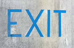 Exit on concrete wall. Exit sign painted on a weathered concrete wall Stock Photography