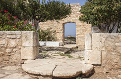 Exit frrom Monastery at Aptera, Crete. View of step and doorway at Monastery of St John Theologusat Aptera, Crete with ruins in the background.  A peaceful Stock Photography