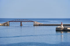 The exit from the Grand harbor, Valletta, Malta. The view of the exit from the Grand Harbor with new Breakwater bridge and the Ricasoli Lighthouse,  Malta Royalty Free Stock Images