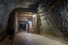 Exit from illuminated underground mine tunnel Stock Photos